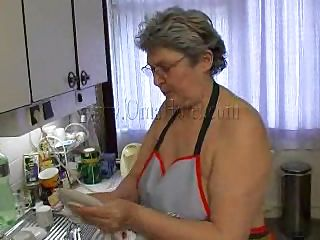 Hot granny Gerlinde washes the dishes naked, wearing only a kitchen gown. She becomes turned on because she has not played for a while now. The old slut starts squeezing her saggy boobs and takes off her white panties so that she could reach more easily her wet cunt. What`s she doing laying naked on the floor?