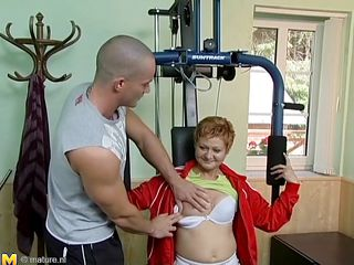 Watch this hot red headed cougar who takes advantage of this young gym instructor. She has great sex experience and starts seducing him, like she well knows. This old babe has all she needs to make a man happy. She starts taking off her clothes to turn the young stud on. He likes playing with her tits.