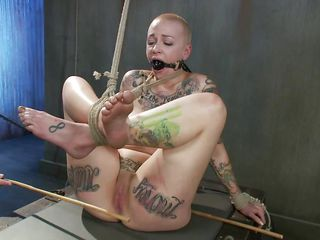 Punk slut Sparky thought she as a bad girl, shaving her head and covering that sexy body with tattoos. Well know, this guy shows her what bad is all about and ties her young body before performing a punishment. He spanks her feet and thighs with a stick and to really teach her a lesson, the guy rubs her pussy too