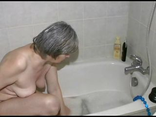 Yeah, this old bitch washes her saggy tits and belly. She's a dirty old slut that needs to wash her pussy really hard. Look at her how slow she gets in that bath tub. Watch out bitch, don't break a hip or something. Let's see how she washes that fucked up body of hers