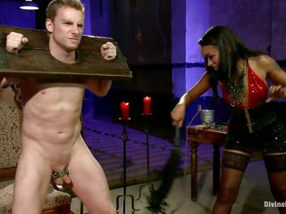 Queen Skin Diamond bound Sebastian Keys with fetters. The ebony goddess whips his tiny cock until its raw and red. She makes him beg for more and squeal like a perverted little piggy as she clamps his nipples and puts clothespins all over his body.