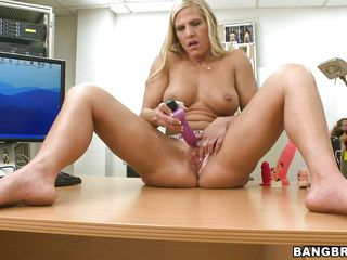 She's a blonde horny slut and gets naked so she could masturbate. Look at her how she spreads her sexy thighs right there on the desk and fills her shaved cunt with that dildo without caring that someone watches her. Well this guy paid her attention and his cock got hard so now she's gotta suck it!