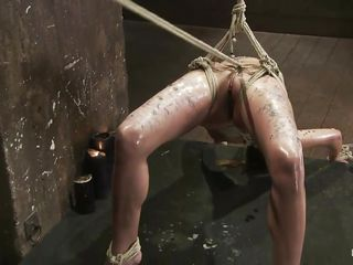 A harsh punishment is barely enough for her, she could use something even more painfully and her pretty face asks it! She's hanging there, tied with rope that goes between her pussy lips. Her executor pours hot wax inducing a lot of pain and to be sure that she's suffering metal clamps are added on her hard juicy nipples. Look..