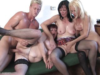 Look at these mature bitches with their big boobs and hard nipples. They are enjoying foursome party with a muscled hard dick guy. One bitch is getting her pussy rubbed by one of the old lady and the other mature whore is getting her pussy drilled by that hard dick from behind right on the couch.