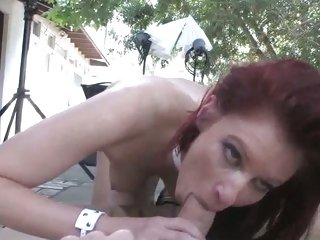 Voluptuous redhead shoves a huge dick down her throat