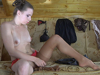 Doll-faced sweetheart matching her bright lacy garter with sheer suntan nylons