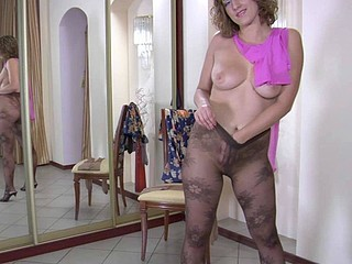 Gorgeous curly chick having fun from putting on various expensive hose
