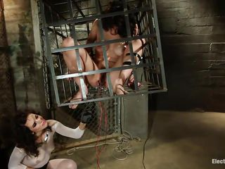 Sexy brunette is placed in a cage by horny Raven who dominates her with pleasure. She kneels to watch Bobbi`s hairy pussy and conquer her with electric wand. Then, she switches toys and makes her tremble with an electric vibrator. Check out how the bitch enjoys having her pussy feeling the vibes!