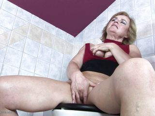 Juliana said she had to go to the toilet, but didn't say why and sure as hell didn't say she'd take so long! What she really needed to do was rub and finger her pussy, and that's what she's up to. She gets her tits out and plays with her old cunt. A guy peeks in through the door and sees her.