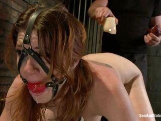 Cici Rhodes loves the dungeon. Strapped to a board, bound and gagged the brunette receives a punishment with hot wax and spanking. Her master removes a metal plug from her ass, then re-inserts it, attaching a rope from it to her head. A vibrator runs over her pussy, making her want to cum, but can't yet.