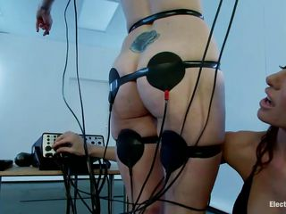 A sexy redhead with nice boobs and a shaved pussy is tied in front of this naughty brunette. Her body is covered with electrodes and she's getting some stimulation through them and also from that vibrator the brunette is using to rub her clitoris. Look at her moaning and receiving all the socking pleasures she wants.