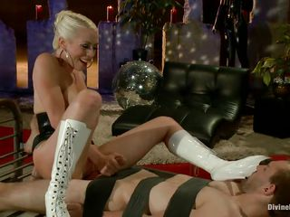 Lorelei Lee has Blake tied to a metal bed, teasing him and laughing as she sticks her pussy almost within reach of his tongue. He's tied down securely and can't get there and she knows it. She traps his dick with her bootheels and sucks him a bit. Then she orders him to lick her boots clean!
